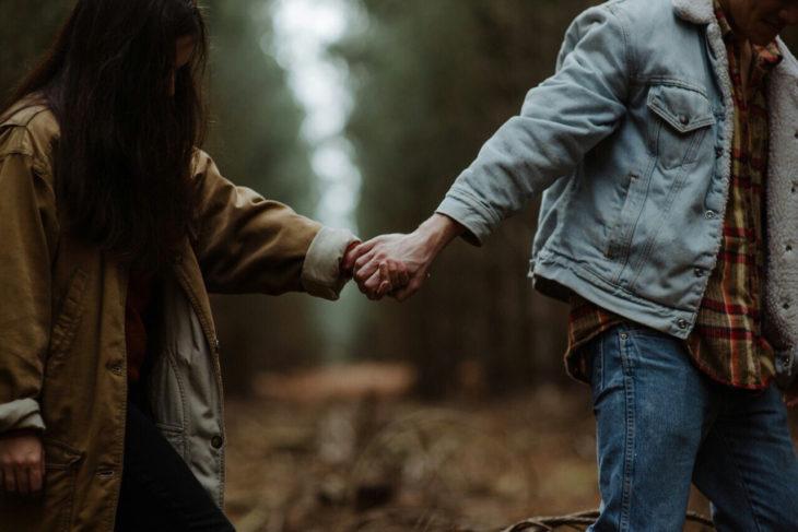 novios caminando en el bosque tomados de la mano