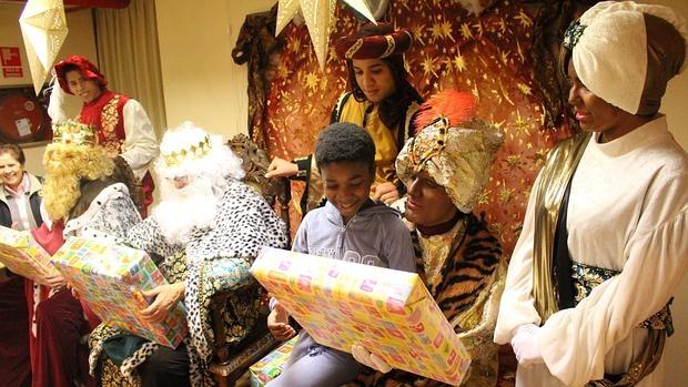 Reyes magos entregando regalos a los niños