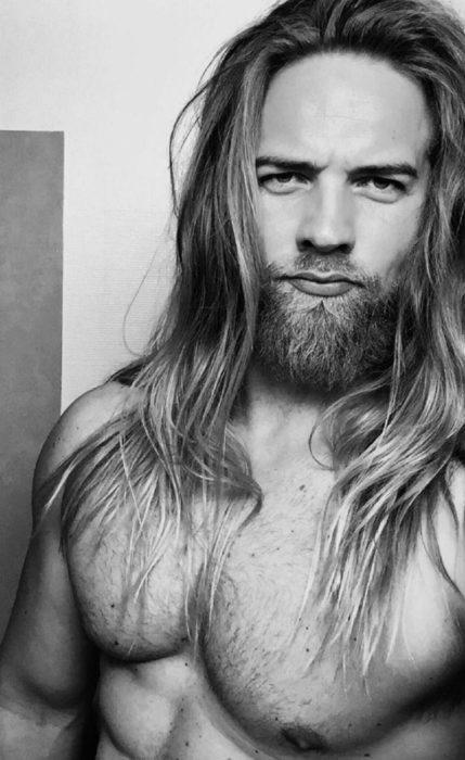 hombre sin playera con cabello largo y barba