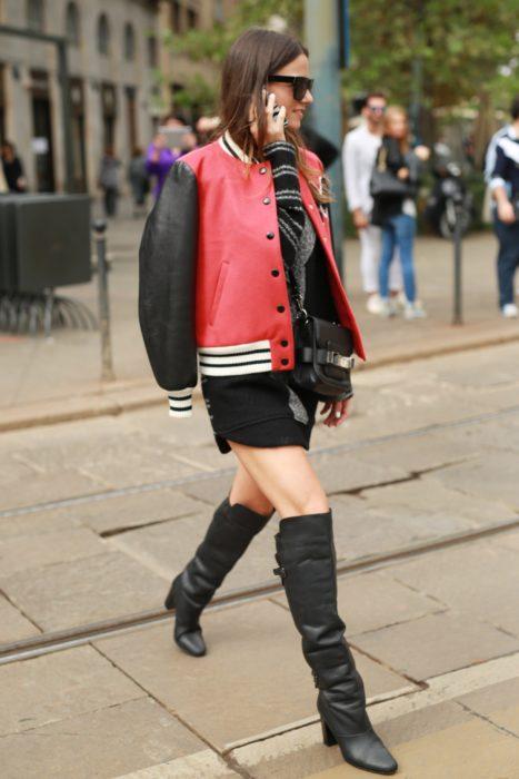 Chica usando una chaqueta de cuero roja y botas altas