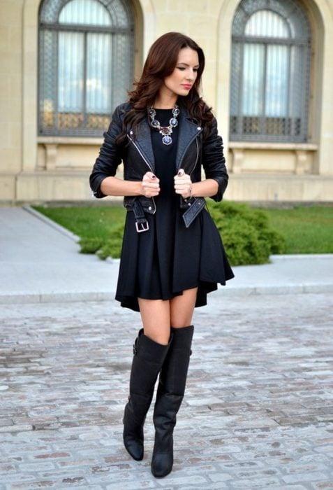 Chica usando un vestido negro con botas