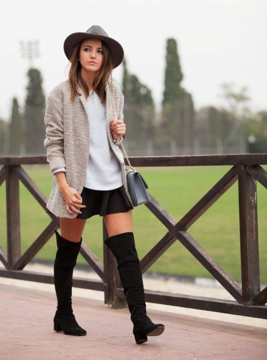 Chica con una falda corta y botas altas