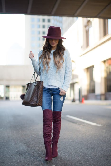 Chica con jeans, suéter, sombrero y botas altas