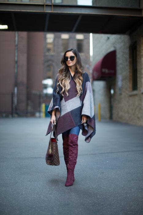 Chica usando un poncho, jeans y botas altas