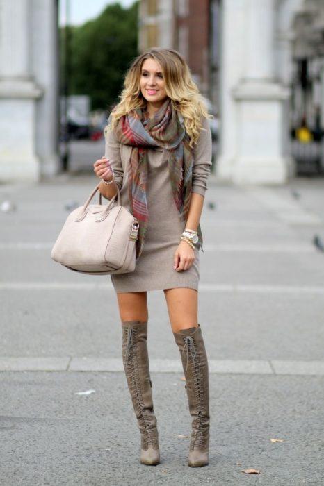 Chica usando un vestido y botas altas