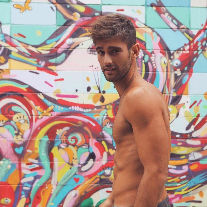 hombre sin playera y pared de colores