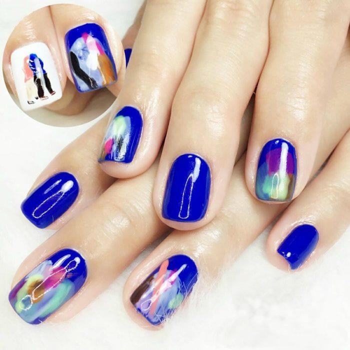 manos de mujer con uñas pintadas de colores