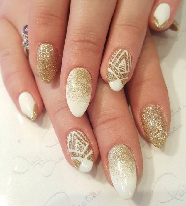 manos de mujer con uñas blancas y dorado
