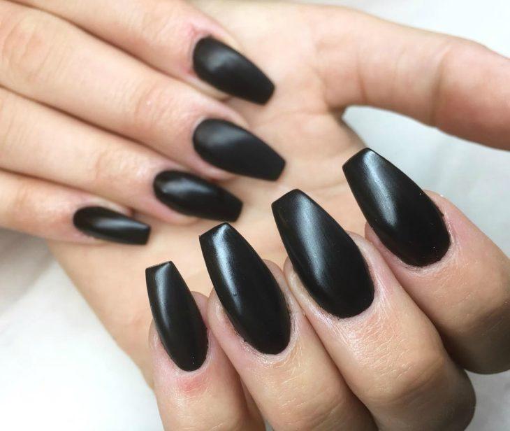 manos de mujer con unas negras en forma de ataud