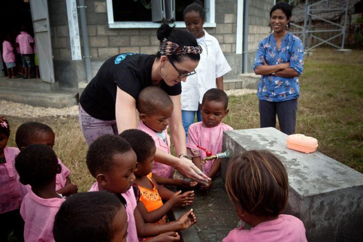 chica generosa ayudando niños