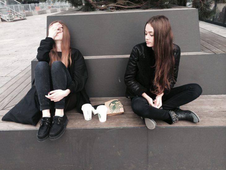 amigas enojadas sentadas en la ciudad