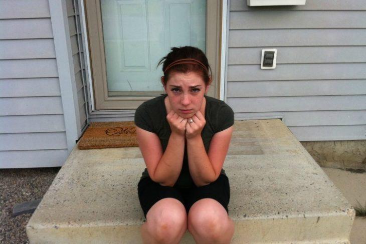 chica sentada en el frente de su casa porque olvido las llaves