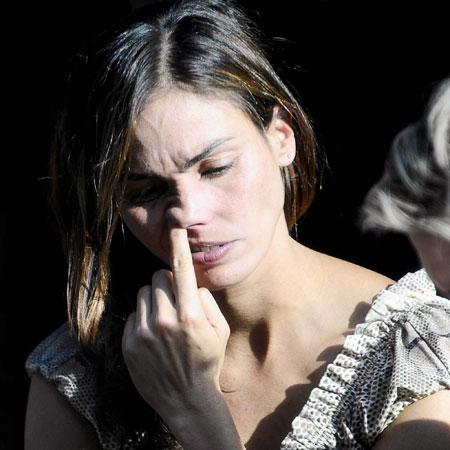 chica hurgando su nariz en la calle