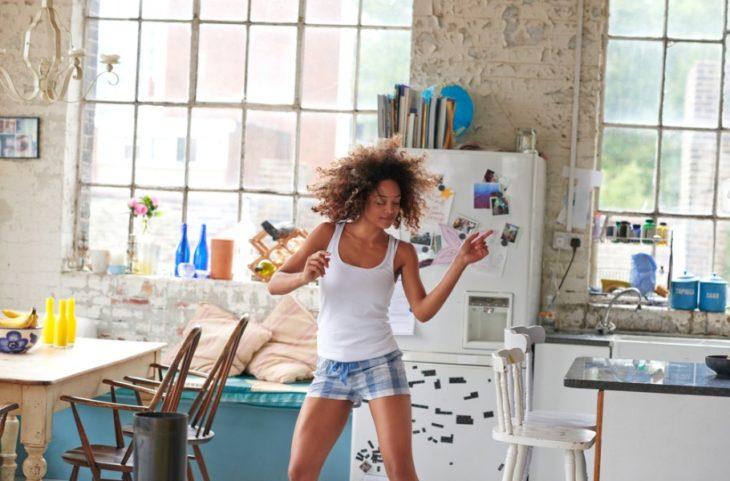 Chica bailando en su departamento