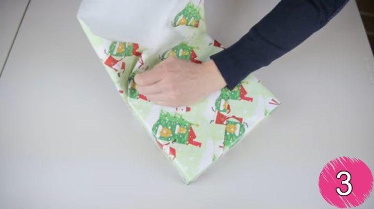 manos de hombre doblando papel de regalo