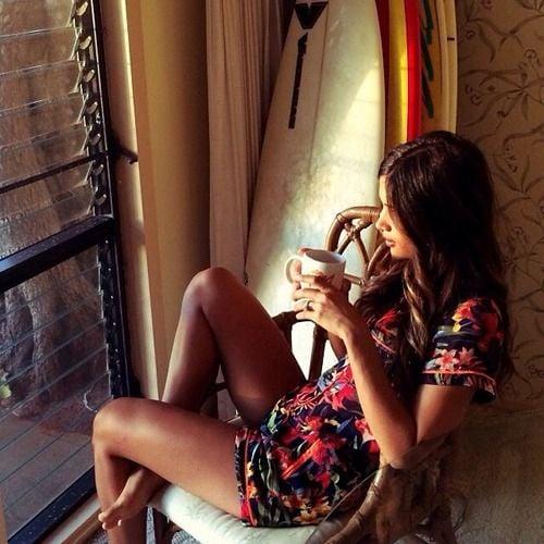 chica tomando café y viendo po rla ventana