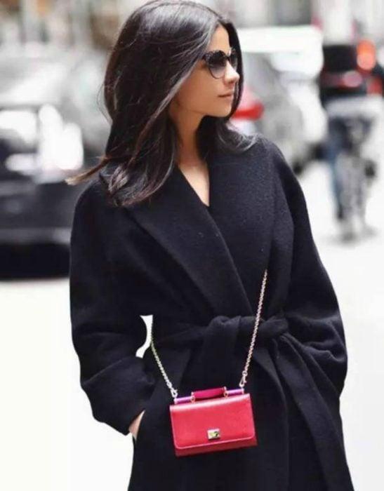 mujer con pequeña bolsa roja