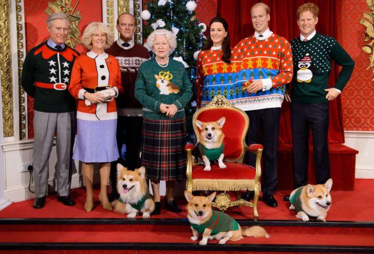 grupo de personas y perros de pie con suéteres navideños