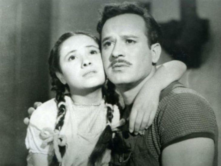 hombre con bigote abraza a niña con trenzas