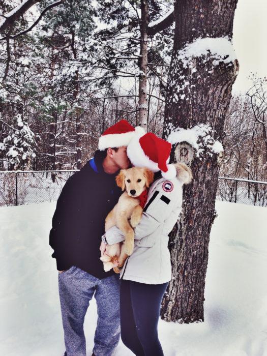 pareja con gorros de navidad cargando a perro