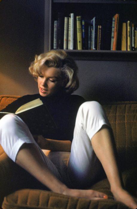 mujer leyendo libros en un sillon