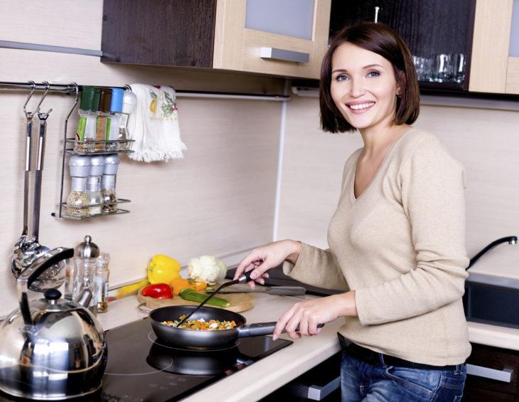 mujer adulta cocinando carne