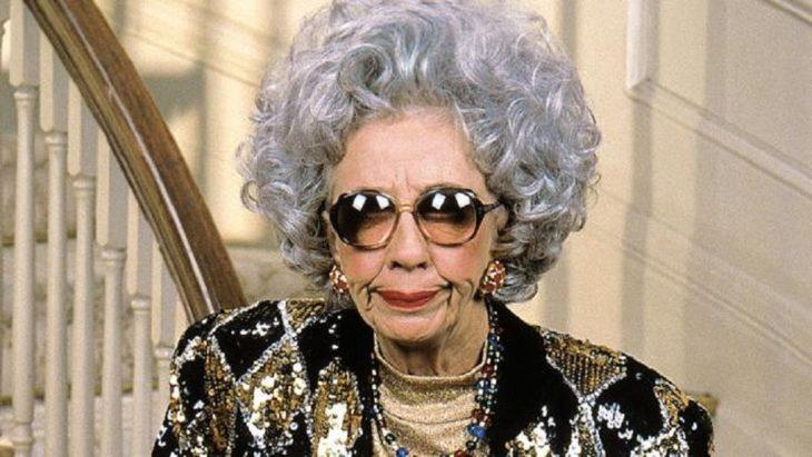 mujer con cabello rizado, canas y lentes