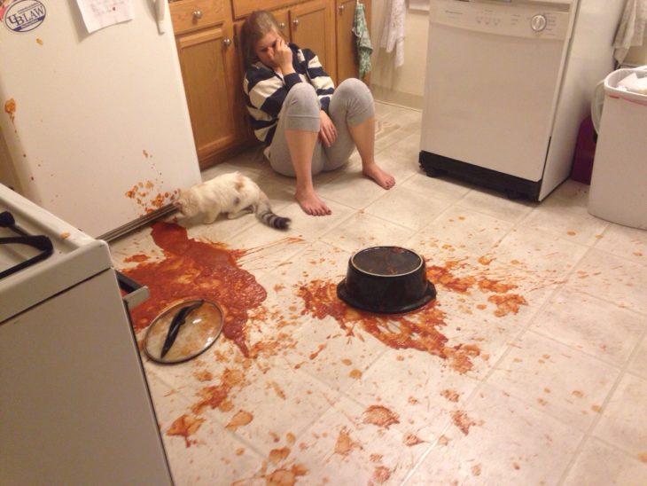 Chica en el piso sucio junto a su gato