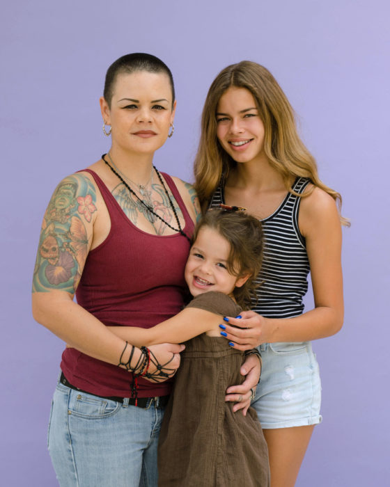 Madre abrazando a sus hijas