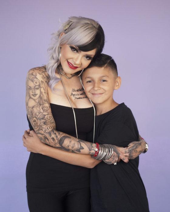 Madre con tatuajes abrazando a su hijo