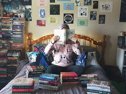 Chica sentada en la cama con libros abiertos para leer