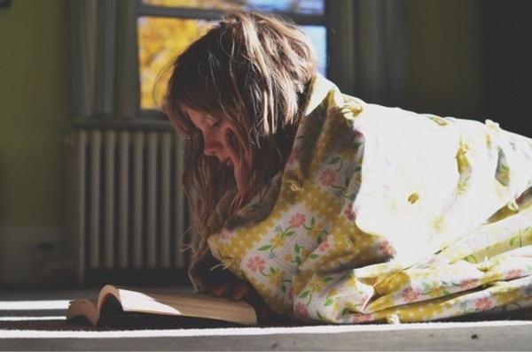 Chica sentada sobre el suelo leyendo un libro