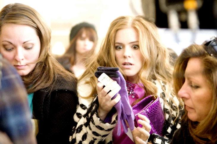 Escena de la película loca por las compras. Chica viendo el precio de unos guantes