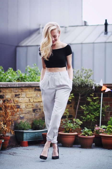 mujer con top negro y pantalon blanco