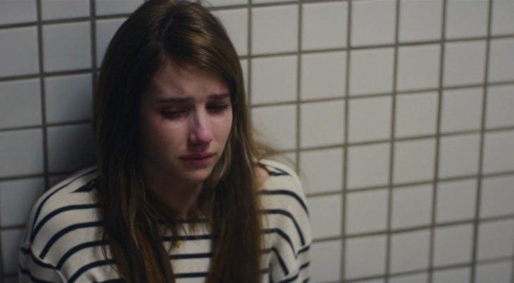 Chica recargada en la pared llorando