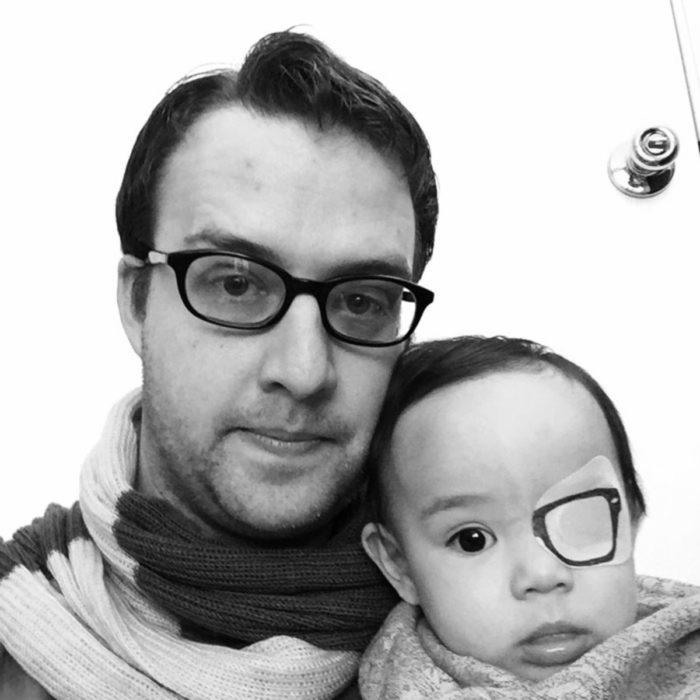 hombre con lentes al lado de bebe con un parche dibujado de lente