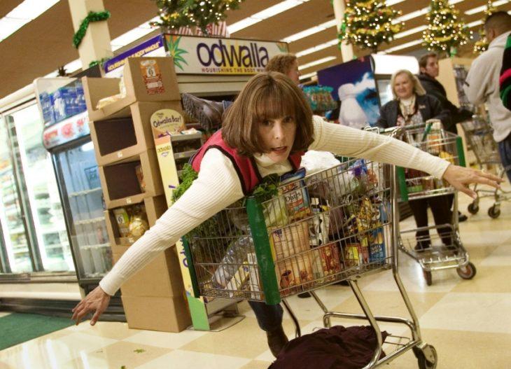 mujer arriba de un carrito de supermercado