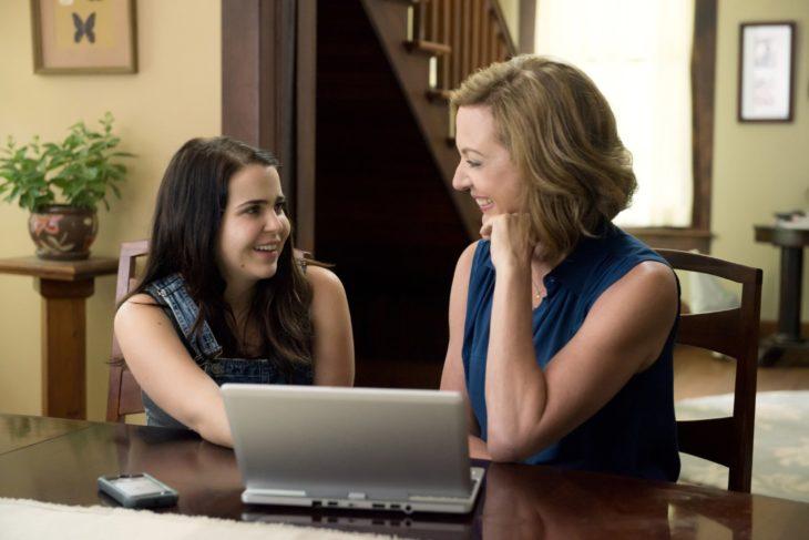 mujer sentada con computadora y chica sonriendo