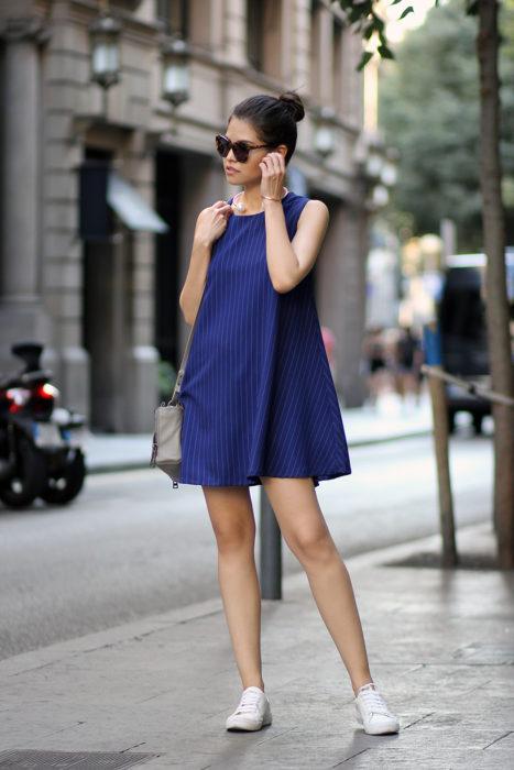 Chica usando un vestido color azul con tenis