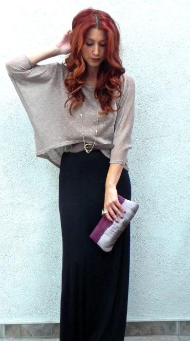 mujer pelirroja con falda negra y top gris