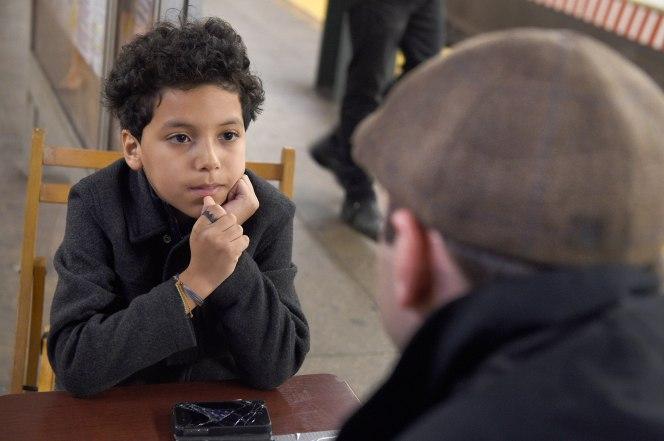 Niño sentado frente a un adulto mientras ambos conversan