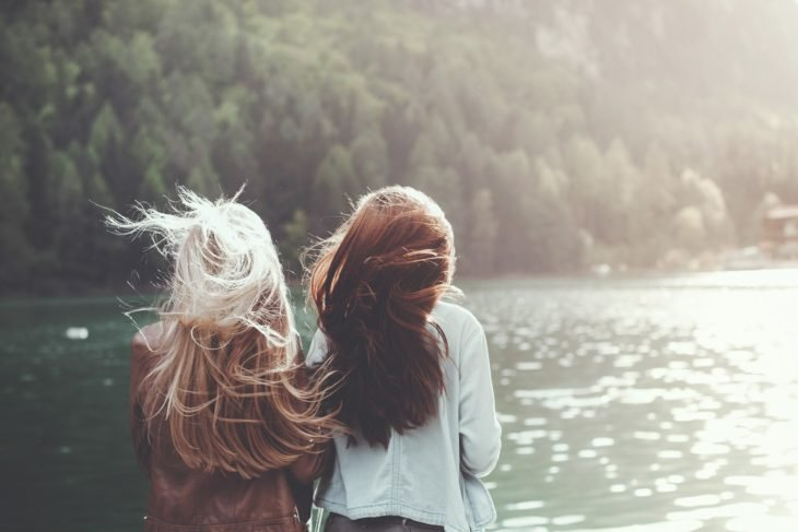 mejores amigas viendo el rio en un atardecer