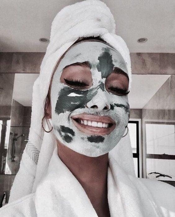 Mujer feliz con mascarilla en el rostro y toalla en la cabeza
