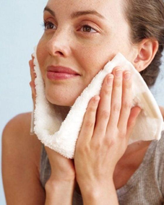 Chica limpiando su rostro con una toalla