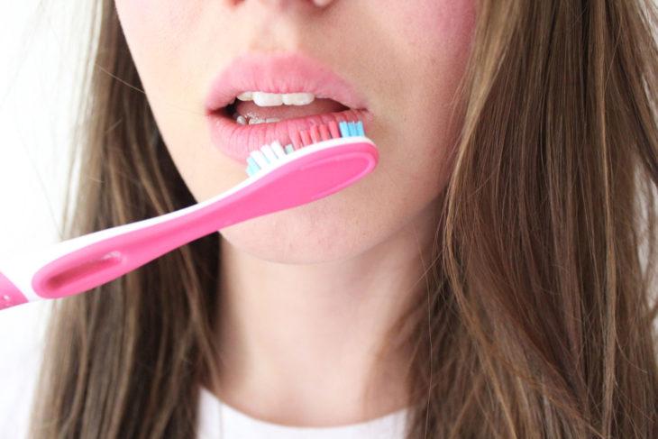 Chica exfoliando sus labios con cepillo
