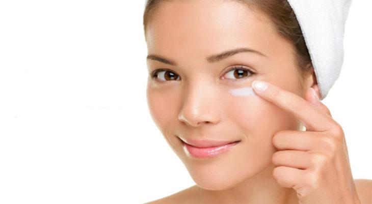 Chica aplicando crema abajo de los ojos