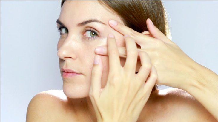 Chica aplicando aceite en el rostro