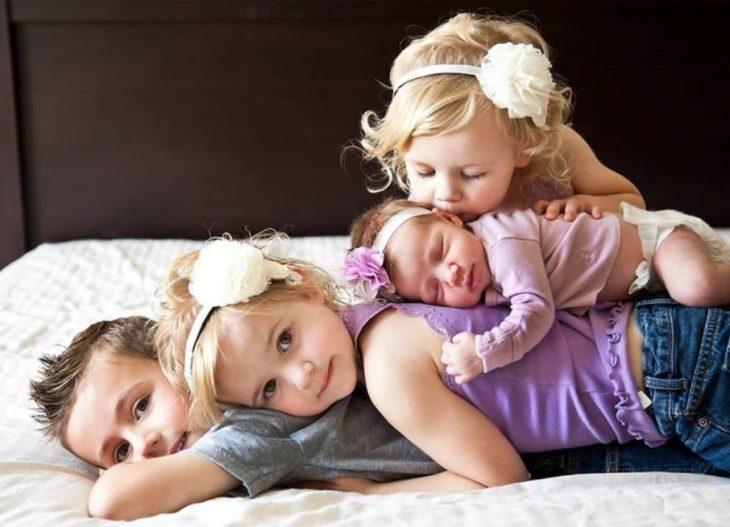 Hermanos recostados en la cama abrazados
