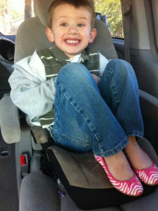 niño rubio sonriendo con zapatos rosas