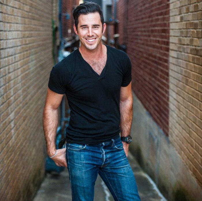 hombre con playera negra y jeans en callejon